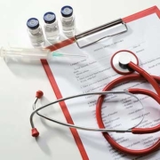 Syringe, three vials with clear liquid on top of medical forms on a clipboard – zoomed out