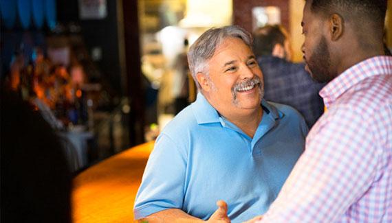 Two men talking in a bar