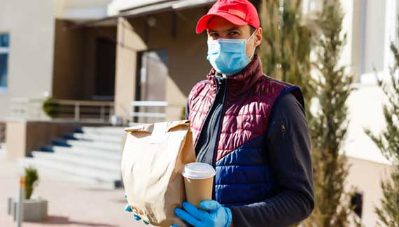 Man walking down street with medical mask and gloves to protect against COVID-19
