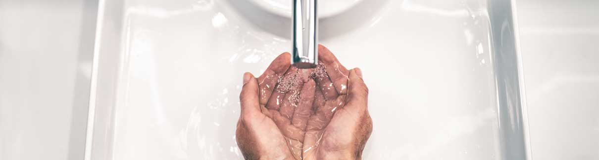 Man washing his hands in sink
